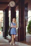 站立在有一个大时钟的房子下的美丽的白肤金发的妇女在一件蓝色礼服和起动穿戴了,谦虚和害羞 库存图片