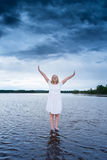 站立在有一场强有力的风暴的一个湖的少妇在她后 库存照片