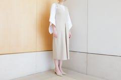 站立在有中间脚跟鞋子最小的时髦样式的壁角米黄礼服的妇女 免版税库存照片