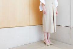 站立在有中间脚跟鞋子最小的样式的壁角米黄礼服的妇女 库存照片