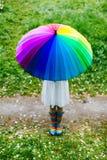 站立在有五颜六色的彩虹伞的开花的庭院里的女孩 春天,户外 免版税库存图片