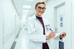 站立在有剪贴板的医院走廊的微笑的医生 库存照片
