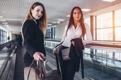 站立在有去离开休息室的重的袋子的移动的走道的两个女性商务伙伴 库存图片