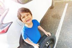 站立在有备用轮胎的汽车旁边的愉快的男孩 库存图片