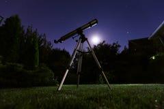 站立在有夜空的后院的望远镜在背景中 天文和星观察概念 免版税图库摄影