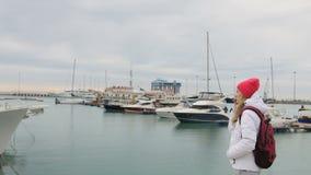 站立在有小船的一个码头和谈话的年轻美丽的白种人女孩对手机 股票视频
