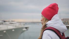 站立在有小船的一个码头和谈话的年轻美丽的白种人女孩对手机 股票录像