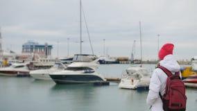站立在有小船的一个码头的年轻美丽的白种人女孩 影视素材