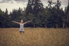 站立在有开放她的胳膊的传播的草甸中间的妇女 免版税库存图片