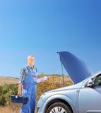 站立在有开放敞篷的一辆残破的汽车附近的技工,在路 免版税库存照片