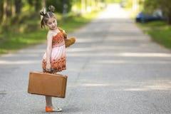 站立在有手提箱和玩具熊的路的快乐的小女孩 愉快 库存图片