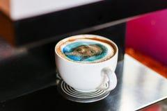 站立在有打印的面孔的打印机的咖啡杯在泡沫 库存照片