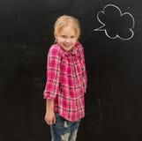 站立在有拉长的云彩的黑板前面的逗人喜爱的矮小的女小学生 免版税库存图片
