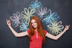 站立在有拉长的五颜六色的花的黑板的快乐的妇女 免版税库存照片