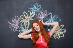 站立在有拉长的五颜六色的花的黑板的愉快的妇女 免版税库存照片