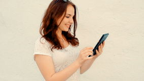 站立在有数字式片剂的墙壁和看的微笑的女学生屏幕前面 影视素材