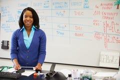 站立在有数字式片剂的Whiteboard的理科教员 免版税库存图片