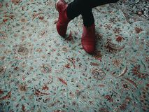 站立在有时尚红色鞋子的一张五颜六色的东方样式地毯的妇女 图库摄影