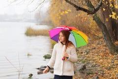 站立在有明亮的五颜六色的彩虹伞的秋天公园的美丽的青春期前的女孩 免版税库存图片