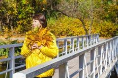 站立在有束的桥梁的美丽的老妇人叶子 免版税库存照片
