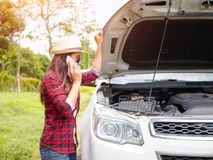 站立在有残破的汽车的路一边的少妇 免版税库存照片