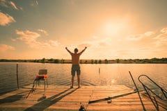 站立在有湖的码头和天空的愉快的人在背景,太阳中 库存照片