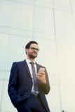 站立在有电话的办公室前面的一套时髦的衣服和太阳镜的愉快的年轻人 免版税库存照片
