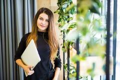 站立在有笔记本的办公室墙壁的愉快的美丽的妇女 企业例证JPG人向量 库存图片