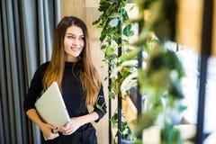 站立在有笔记本的办公室墙壁的愉快的美丽的妇女 企业例证JPG人向量 免版税库存图片
