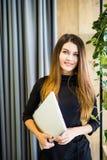 站立在有笔记本的办公室墙壁的愉快的美丽的妇女 企业例证JPG人向量 免版税库存照片