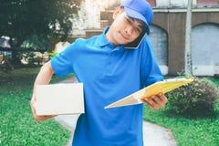 站立在有箱子的房子前面的送货业务传讯者 免版税图库摄影