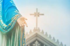站立在有耶稣受难象或十字架的天主教主教管区前面的保佑的圣母玛丽亚雕象的手 免版税库存照片