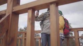 站立在有背包的桥梁的游人年轻夫妇在他们的后面 采取在他的有胡子的人一selfie 股票录像
