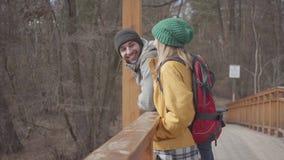 站立在有背包的桥梁的青年人的画象在他们的后面 有胡子的男人和俏丽的妇女 影视素材