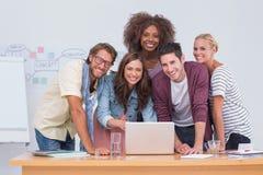 站立在有膝上型计算机的书桌的创造性的队 免版税库存照片