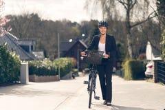 站立在有自行车的街道上的女实业家 图库摄影