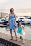 站立在有船的船坞的母亲和女儿 库存图片