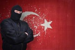 站立在有被绘的国旗的墙壁附近的面具的人  免版税库存图片