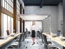 站立在有玻璃证券交易经纪人行情室的开放办公室的妇女在纽约 库存照片