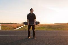 站立在有longboard的路的年轻人在他的手上, 免版税库存图片