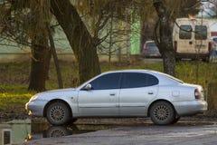 站立在朦胧的绿色树下的一辆新的白色汽车在夏天明亮的天 库存图片