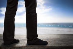 站立在木地板和海边背景的商人 免版税库存照片