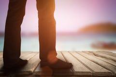 站立在木地板和海边背景的商人 图库摄影