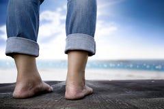 站立在木地板和海边背景的商人 库存图片