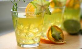 站立在木头的三个黄绿色冰鸡尾酒,装饰用桔子、阳桃、石灰和迷迭香 当事人准备好 免版税库存照片
