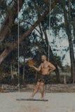 站立在木摇摆的年轻英俊的人 免版税库存照片