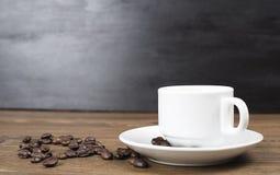 站立在木桌上的咖啡杯正面图用咖啡豆在黑墙壁背景 免版税库存图片