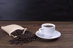 站立在木桌上的咖啡杯正面图用在囊的咖啡豆 库存照片