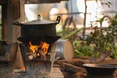 站立在木灼烧的火炉的老罐 免版税库存图片