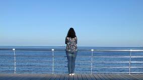 站立在木码头的妇女调查距离 4K被处理的宽框架未加工 股票视频